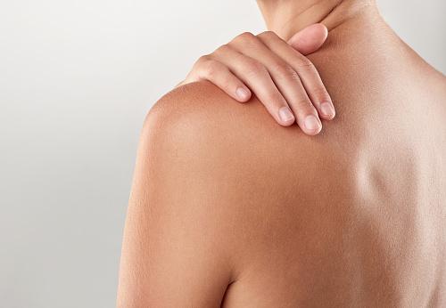 Closeup studio shot of a woman touching her bare shoulder