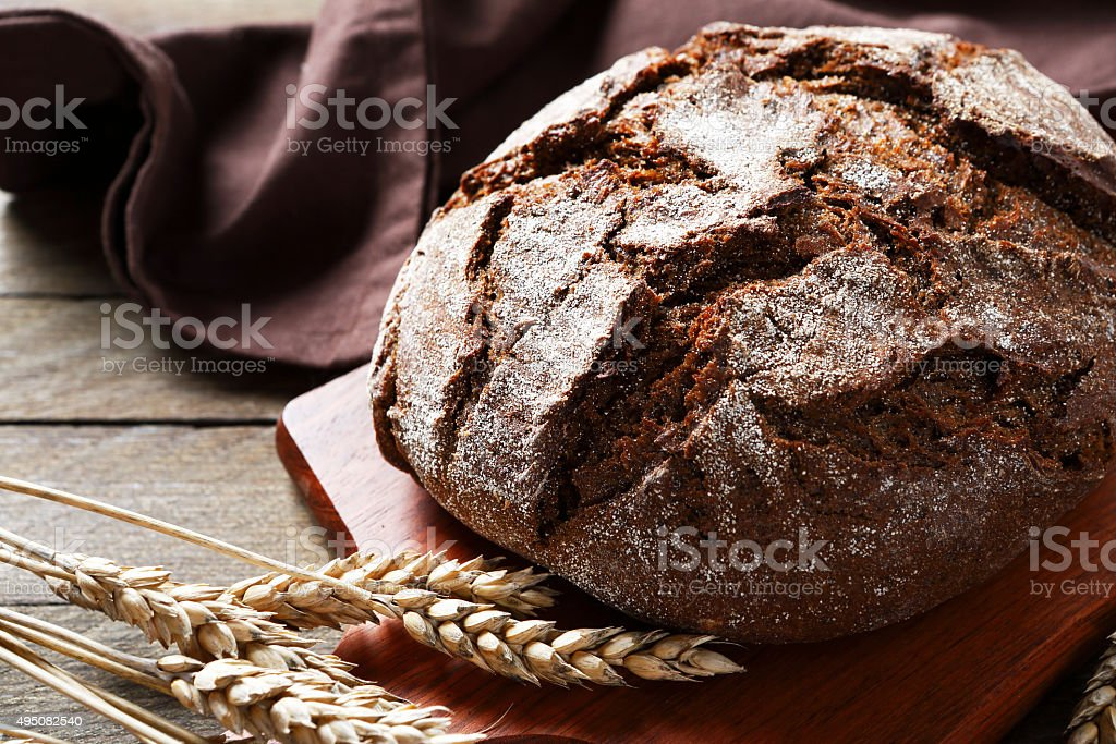 Whole bread on a cutting board stock photo
