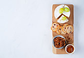 Whole Camembert cheese served with grapes, chutney, cranberry crackers, pecans nuts over wooden kitchen table, light marble background with copy space. Finger food, top view.