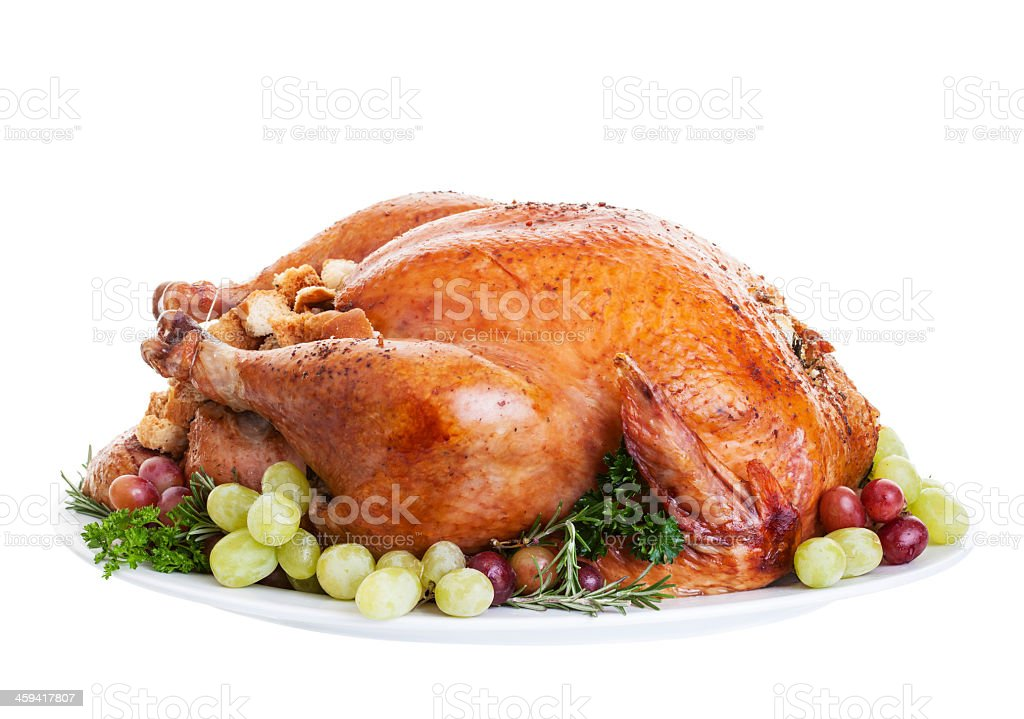 Whole cooked turkey on plate with red and green grapes stock photo