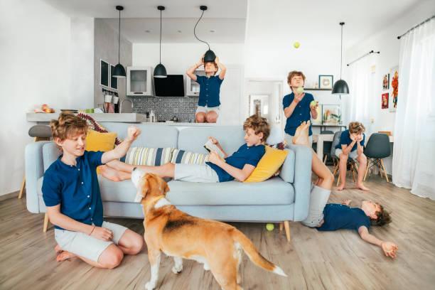 Ganzer Tag auf einem Foto: kleiner Teenager, der quarantänegesperrt ist, zu Hause. Er spielt Hund, liest Bücher, langweilt viel, lernt jonglieren, täuschen. Weltcoronavirus-Pandemie oder zu Hause bleiben Konzept – Foto