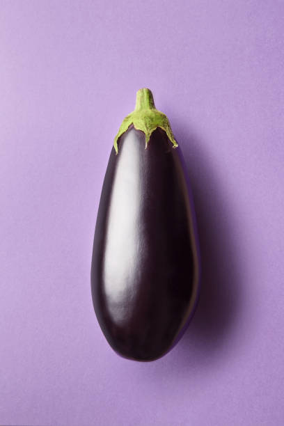 whole eggplant on a purple background viewed from above. top view of an aubergine. copy space - melanzane foto e immagini stock