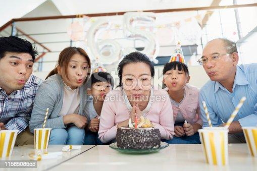 Multi-generation Taiwanese family celebrating grandma's birthday at home.
