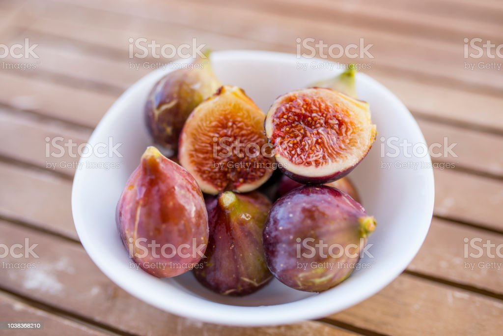 Whole Figs And One Fig Sliced In Half On Top Of A Teak