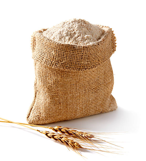 Whole flour in bag with wheat ears stock photo