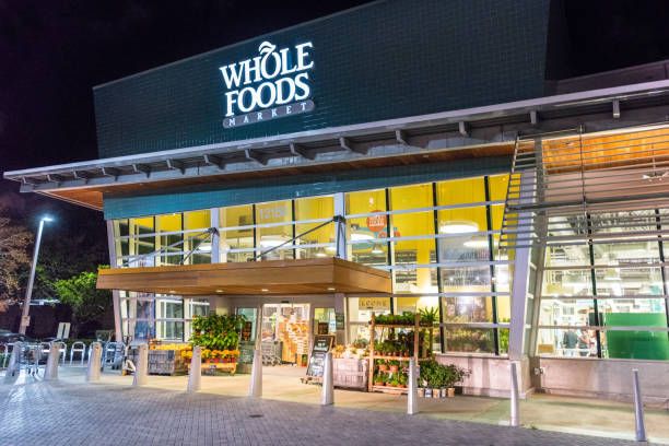 Whole Foods Market North Miami's Whole Foods Market Facade at night. Whole Foods is an American foods supermarket chain specializing in natural and organic foods. It opened on Sept. 20, 1980, in Austin, Texas, its current headquarters. It is owned by Amazon.com entrance sign stock pictures, royalty-free photos & images