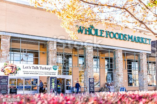 istock Whole Foods Market sign on exterior building in city in Virginia with people, thanksgiving turkey sign, autumn trees foliage and entrance 877930046
