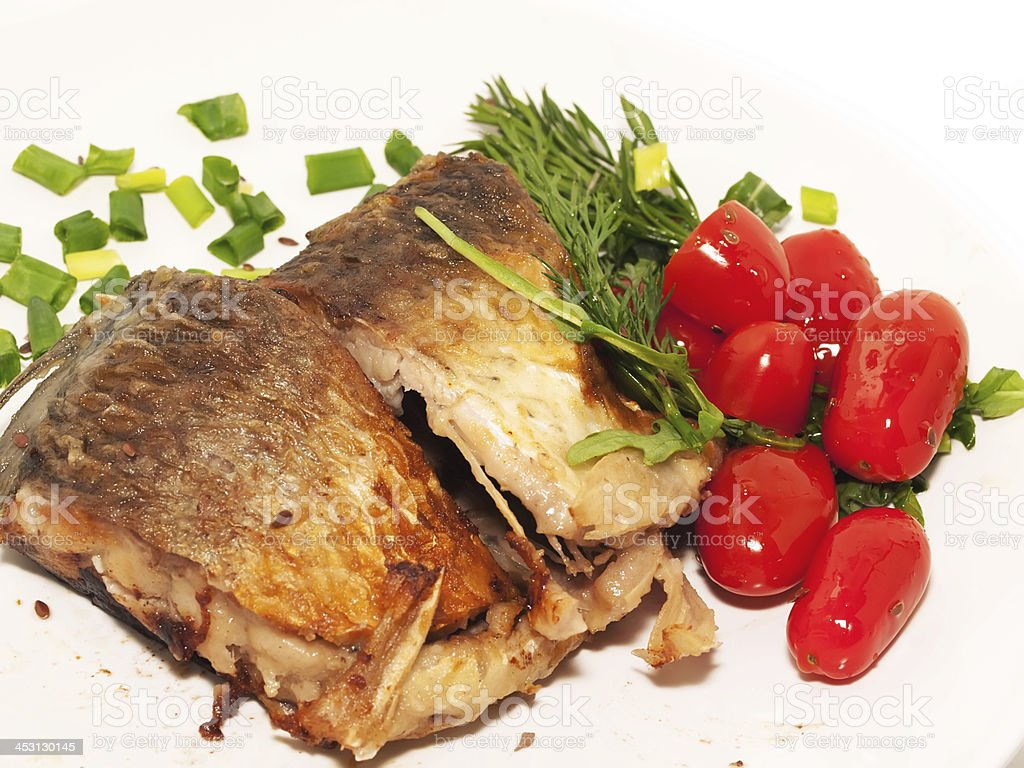 whole fried sunfish over plate with tomatoes royalty-free stock photo