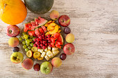 Fruit mix. Apple, peach, grapes, watermelon, cantaloupe, raspberry, plum. Whole fruits and slices on a plate lie on a white wooden background. Copy space, Place for text. Flat Lay