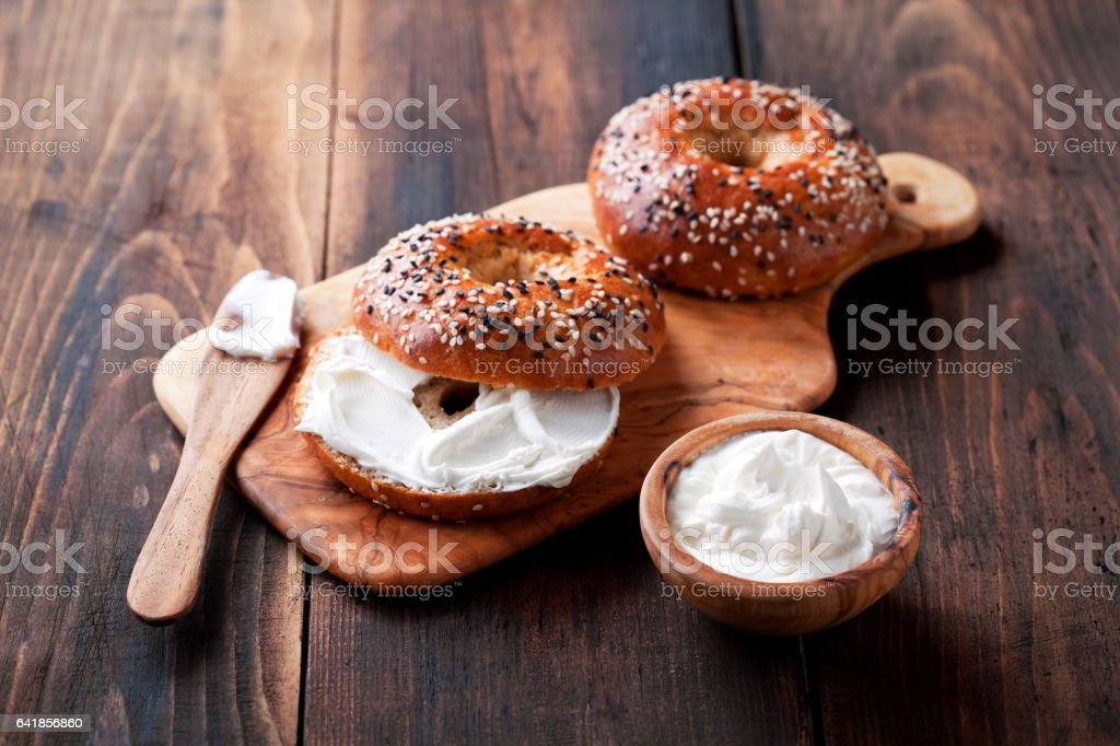 Whole grain bagels with cream cheese on wooden board stock photo