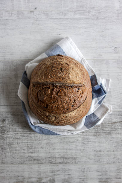 whole grain bread whole grain bread on textured background round loaf stock pictures, royalty-free photos & images