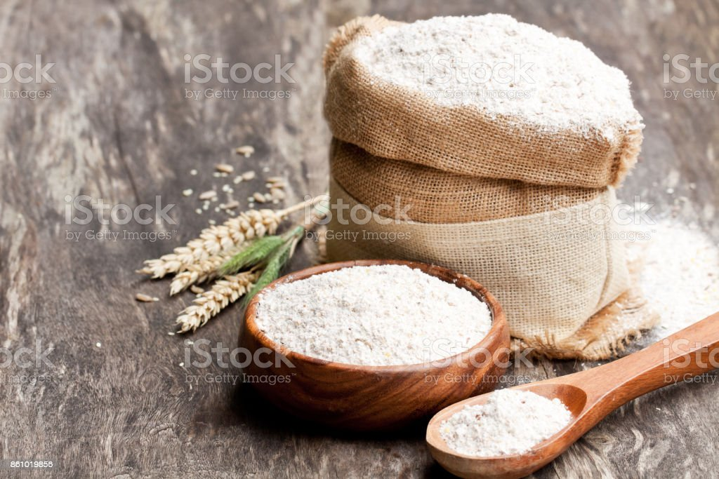 Whole  grain flour in a wooden bowl and sackcloth bagwith ears Whole  grain flour in a wooden bowl and sackcloth bagwith ears Agriculture Stock Photo