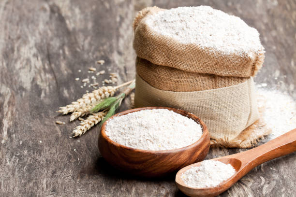 Whole  grain flour in a wooden bowl and sackcloth bagwith ears stock photo