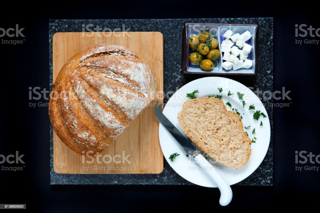 Whole grain loaf with feta cheese and olives stock photo