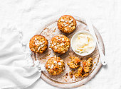 istock Whole grain muffins with dried apricots, oatmeal, apple, carrots and nuts on rustic cutting board on light background, top view. Healthy vegetarian food, dairy free 956969904