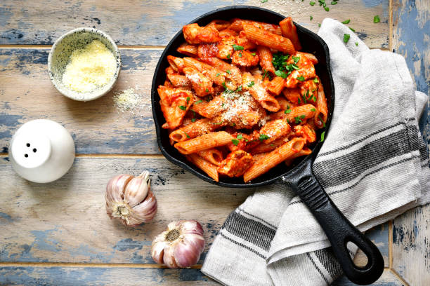 Whole grain pasta with chicken fillet in tomato sauce Whole grain pasta with chicken fillet in tomato sauce in a skillet over old rustic wooden background .Top view. penne stock pictures, royalty-free photos & images