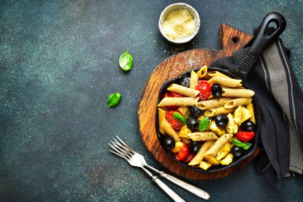 vollkorn-nudeln mit cherry tomaten, schwarzen oliven und huhn - gesunde huhn pasta stock-fotos und bilder