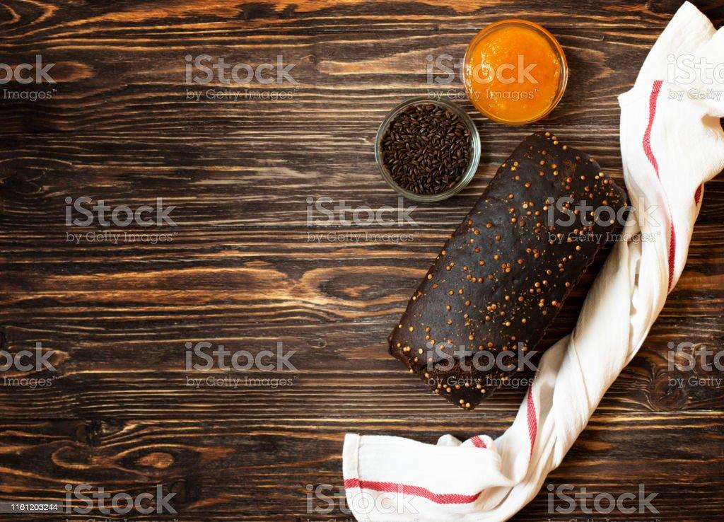 Whole grain rye bread, honey and malt on a dark wooden background....