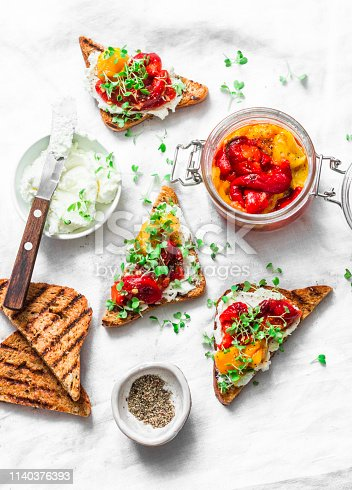 Whole grain sandwiches with marinated pickled roasted grilled sweet pepper, and cream cheese - delicious snack, appetizers, tapas on a light background, top view
