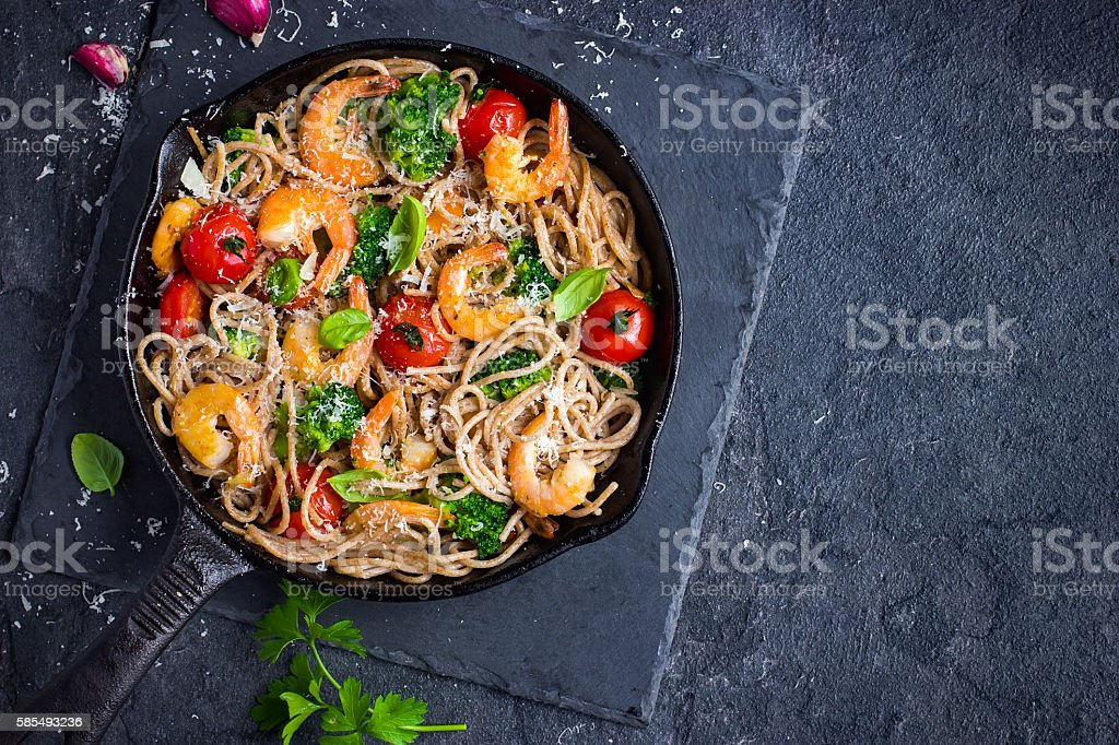 whole grain spaghetti pasta with shrimps and broccoli, top view stock photo