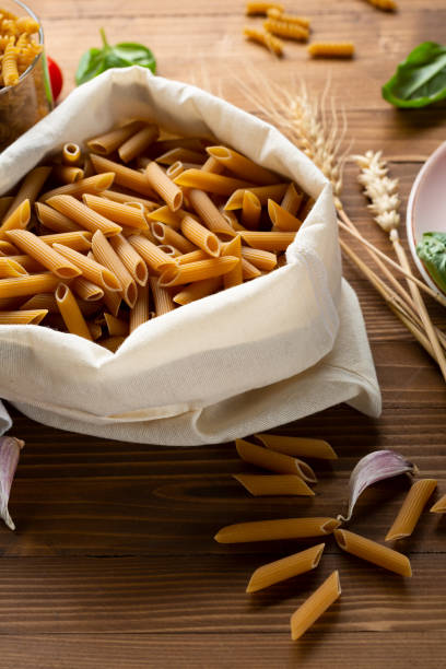 Whole grain uncooked pasta penne in cotton bag close up stock photo