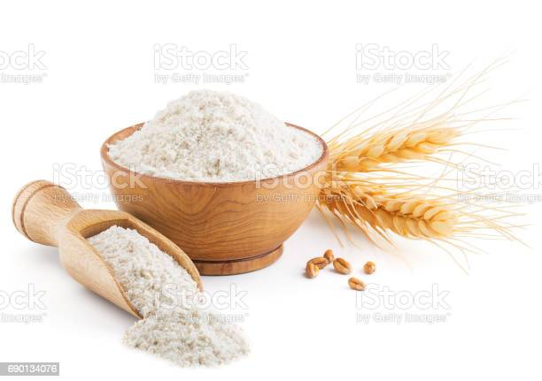 Whole grain wheat flour and ears isolated on white background