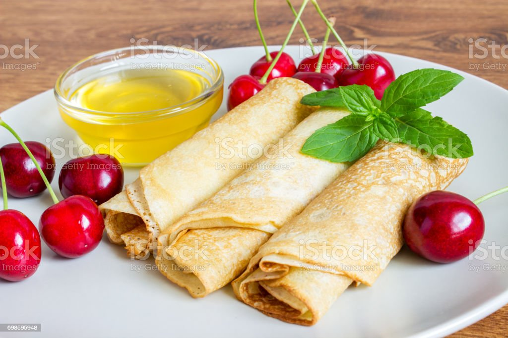 Whole gran pancakes with honey, mint and cherries. Useful breakfast. stock photo