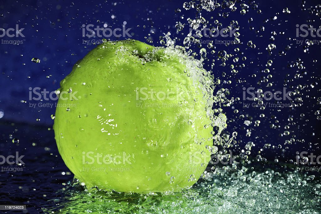 Whole green apple with stopped motion water drops royalty-free stock photo