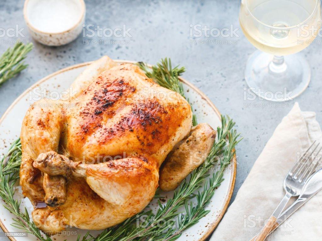 Toda parrilla pollo con piel caramelizada y romero fresco en una mesa. foto de stock libre de derechos