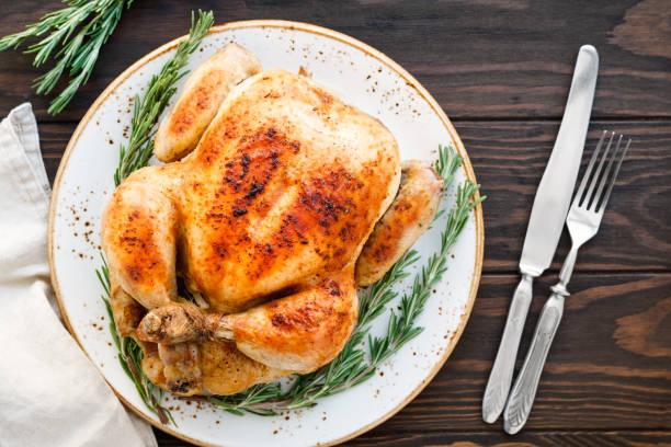 hele barbecue kip met gekarameliseerde huid en verse rozemarijn op een houten tafel. - geheel stockfoto's en -beelden