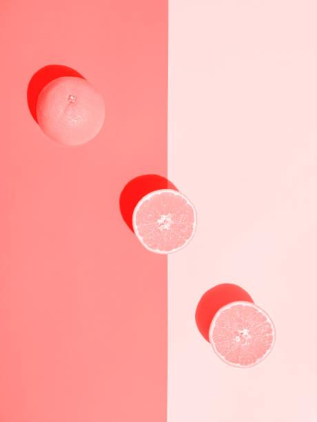 Ganze halbierte, saftige Orange, die in rosa Duotonhintergrund angeordnet ist. Hartes Sonnenlicht harte Schatten. Lebendige Pastellfarben. Sommer tropisches Modekonzept – Foto