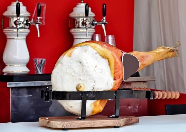 gesamten italienischen bein rohschinken mit seiner schneidebrett auf dem tisch eines balkens. schankanlage bier auf hintergrund - friaul julisch venetien stock-fotos und bilder