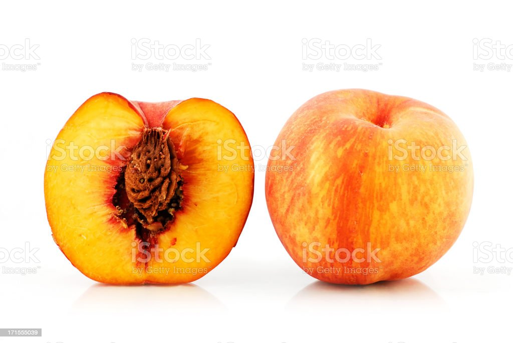 A whole peach and one with the core exposed royalty-free stock photo