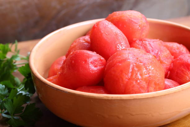whole peeled tomatoes in brown bowl - peeled stock photos and pictures