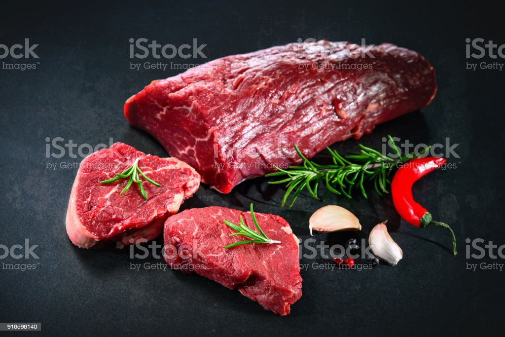 Ganzes Stück Rinderfilet mit Steaks und Gewürzen bereit zum Garen auf dunklem Hintergrund – Foto