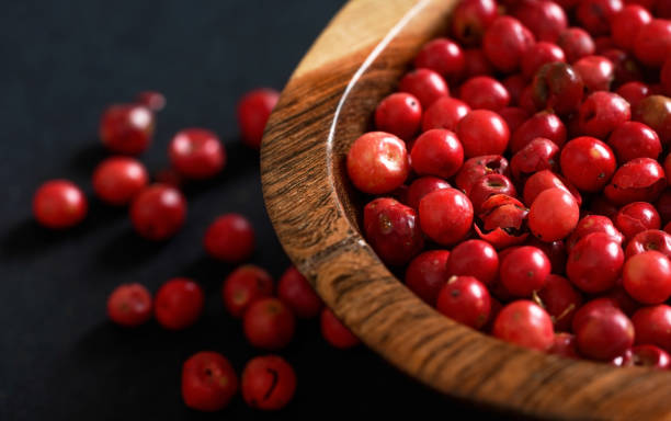 Whole pink red peppercorns in small wooden bowl, some scattered on black gray paper, closeup view from above stock photo