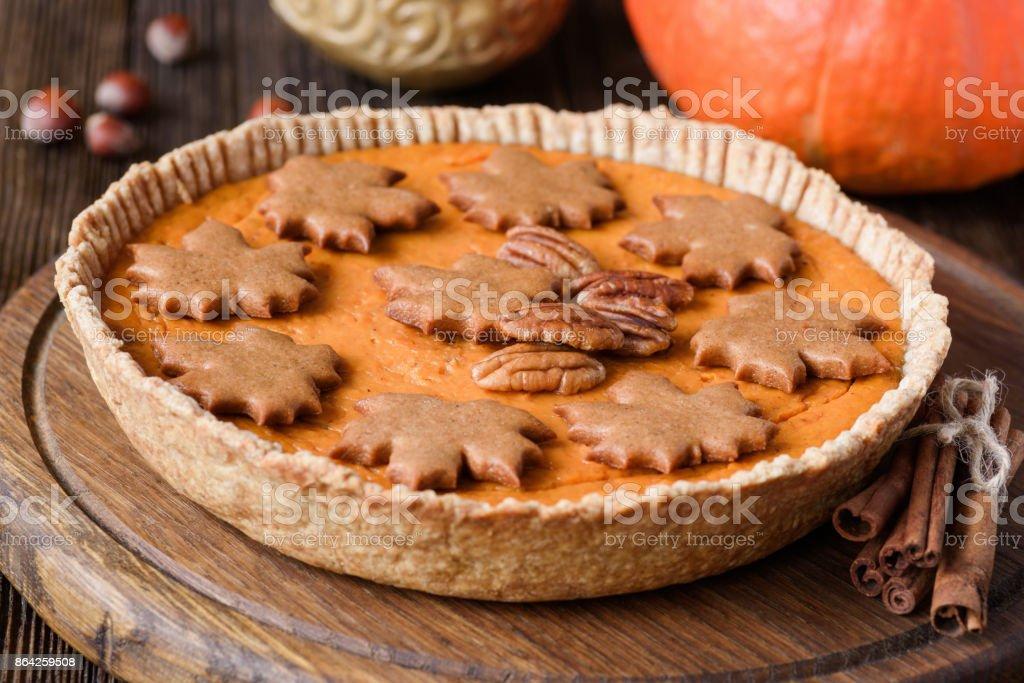 Whole pumpkin pie on wooden board royalty-free stock photo