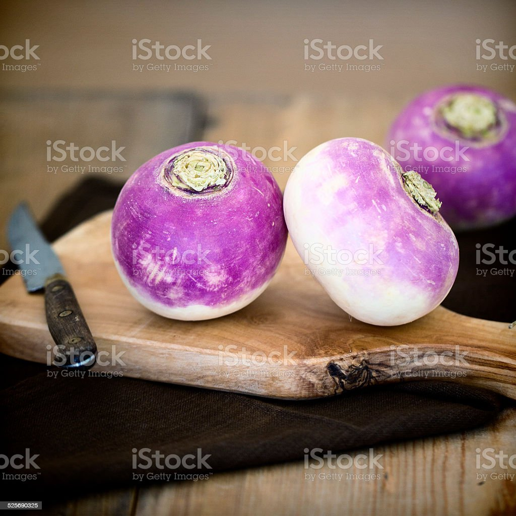 Whole purple headed turnips on wooden cutting board. stock photo