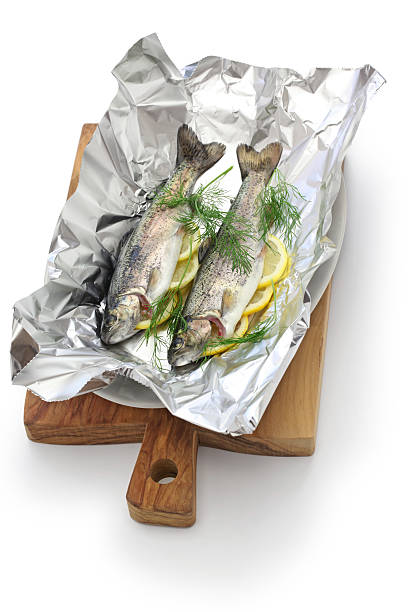 whole rainbow trout baked in foil (before oven baking). - forelle backofen stock-fotos und bilder