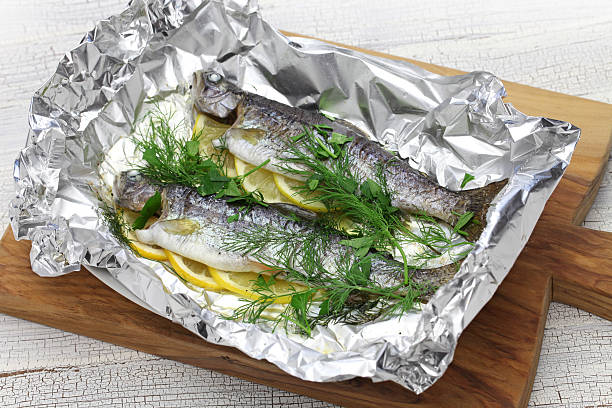 whole rainbow trout baked in foil - forelle backofen stock-fotos und bilder