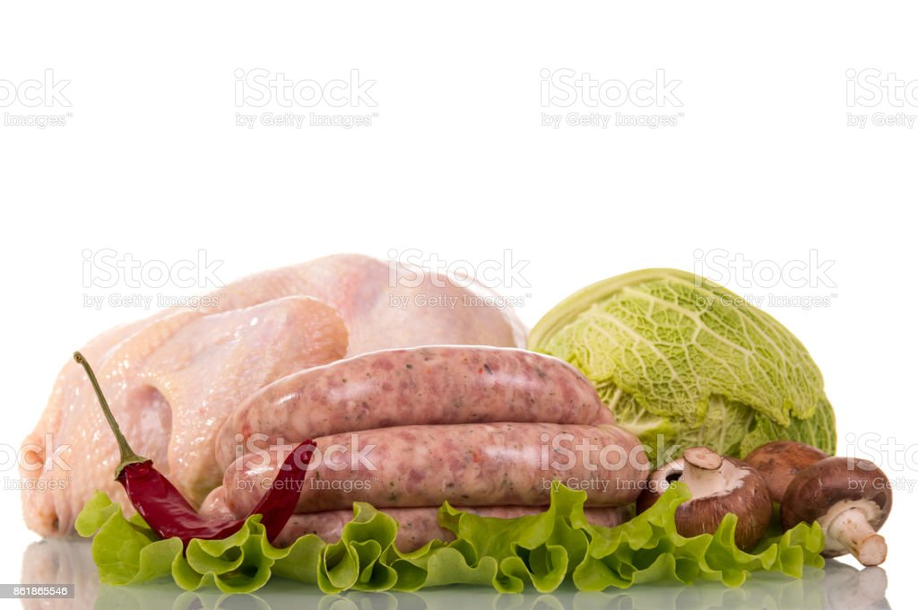 Whole raw chicken carcass, chicken sausages, Savoy cabbage, pepper, mushrooms and lettuce leaves on white. stock photo