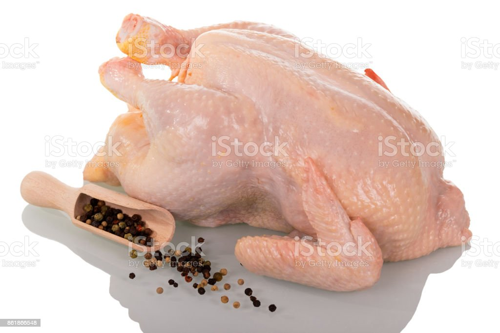A whole raw chicken carcass, scoop with various peppers and scattered on white. stock photo