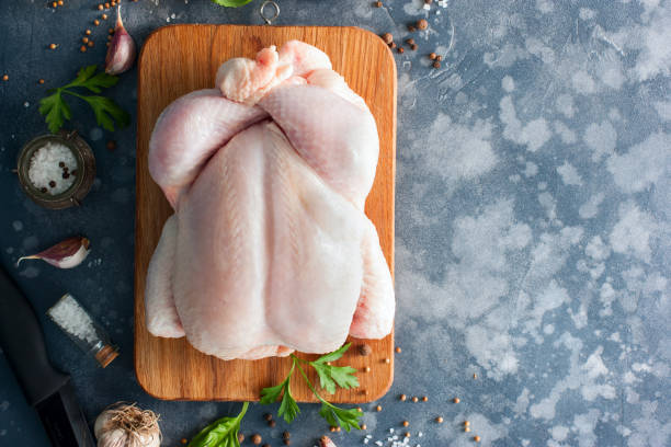 Whole raw chicken on a wooden board with spices for cooking, top view, horizontal, copy space stock photo