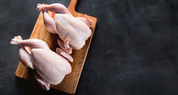 Whole raw chicken Whole raw chicken on wooden cutting board on black background with copy space white meat stock pictures, royalty-free photos & images