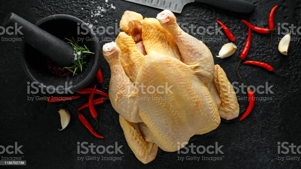 Whole Raw Chicken with seasonings in granite mortar stock photo