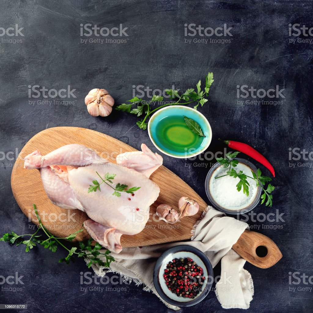 Whole raw chicken with seasonings stock photo