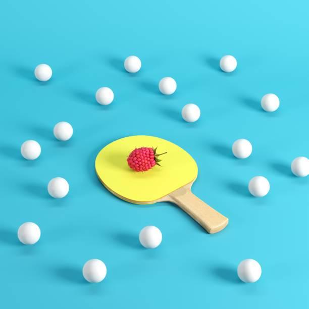 Ganze reife Himbeere auf Tischtennispaddel mit gelbem Gummi, umgeben von weißen Tischtennisbällen auf blauem Hintergrund. Minimales Fruchtgedankkonzept. – Foto