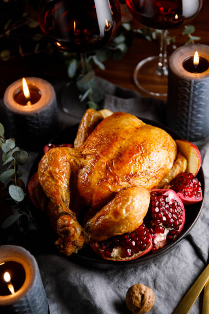 Whole roast chicken with pomegranate, apple and red wine on a festive table. Christmas or New Year cooking concept. stock photo