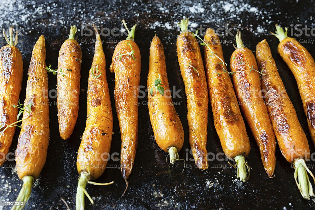 whole roasted carrots with tails stock photo