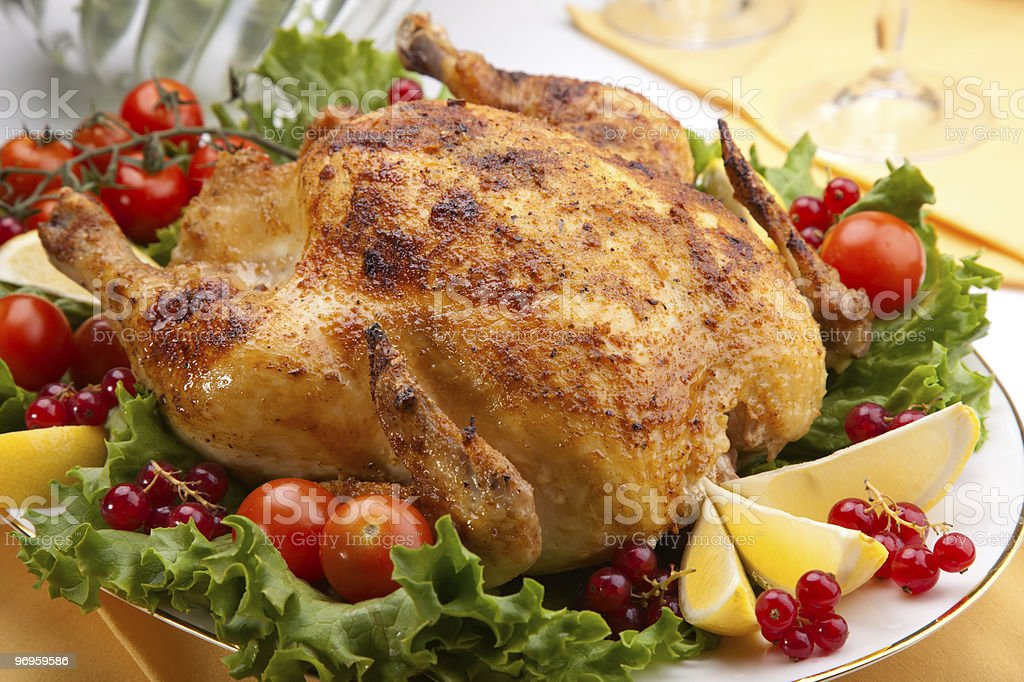 Whole roasted chicken on table stock photo